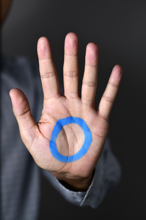 fight disease: a blue circle, symbol of diabetes, painted in the palm of a young man wearing a gray suit, in support of diabetic people Stock Photo