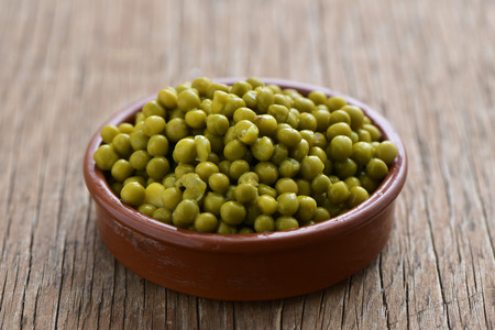 some cooked peas in an earthenware bowl, on a rustic wooden table Stock Photo