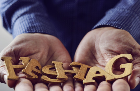 twit: wooden letters forming the word hashtag placed in the hands of a young caucasian man