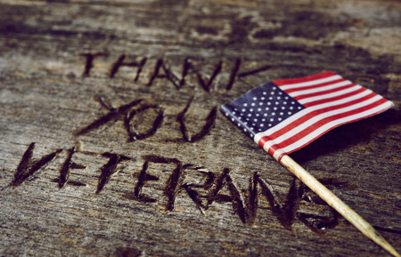 the text thank you veterans carved in a rustic wooden surface and a flag of the United States