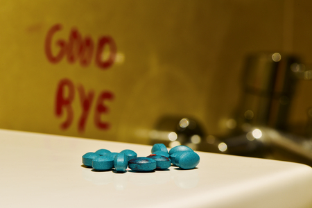 good bye: closeup of a pile of blue pills and the text good bye handwritten in the wall in the toilet
