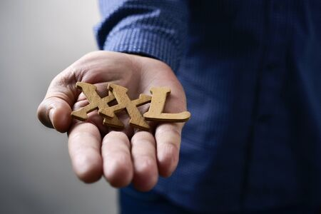 extra large: closeup of some wooden letters forming the expression XXL, for extra extra large, in the hand of a young caucasian man