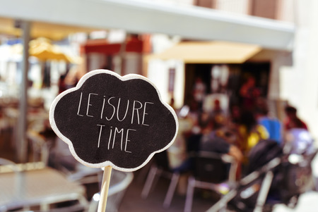 closeup of a thought bubble-shaped signboard with the text leisure time written in it, in front of the blurred terrace of a restaurant Stock Photo