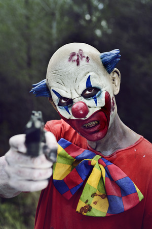 a scary evil clown pointing a gun to the observer in the woods