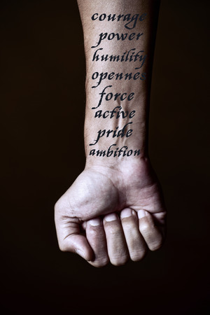 humility: closeup of a young caucasian man with the words courage, power, humility, openness, force, active, pride and ambition, simulating a tattoo in his forearm, against a black background