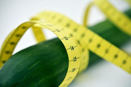 pene: primo piano di un nastro di misurazione intorno ad un cetriolo raffigurante il membro maschile
