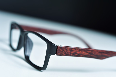 closeup of a pair of plastic and wooden rimmed eyeglasses on a white surface