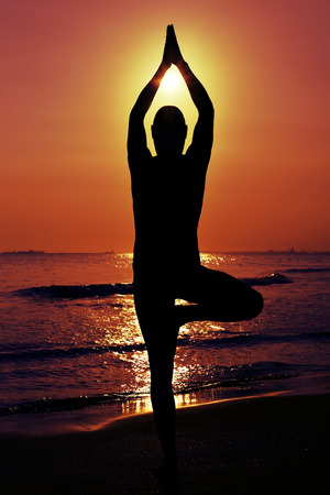 prana: the silhouette of a young yogi man practicing the tree pose in front of the sea in backlight Stock Photo