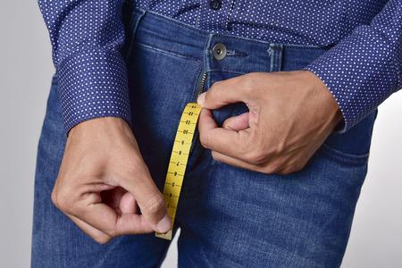 Nahaufnahme eines jungen Mannes, der ein Stück messendes Band hält, das von der Fliege seiner Jeans auftaucht und den normalen Bereich des Penis darstellt