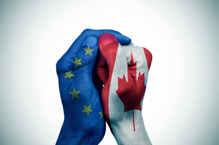 bilateral: a hand patterned with the flag of the European Community envelops another hand patterned with the flag of Canada