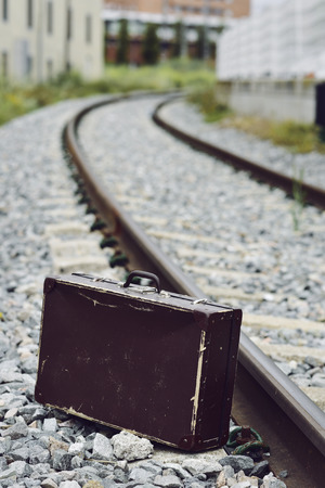 immigrate: an old brown suitcase next to the railroad tracks Stock Photo