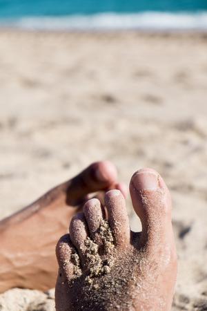 romance: close-up van de voeten van twee jonge mannen spelen footsie op het strand Stockfoto