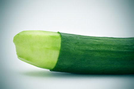 closeup of a cucumber with the skin of its tip removed depicting a circumcised male member Фото со стока
