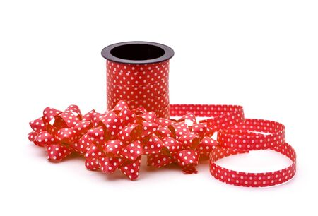 loopy: some gift puff bows made with red ribbon patterned with white dots and a roll of this ribbon, on a white background