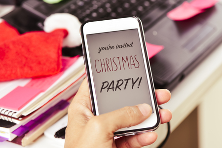 closeup of a young man at his office looking to his smartphone, with the text you are invited christmas party in its screen