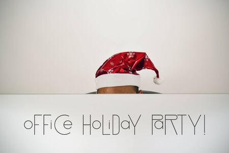 headman: a young caucasian man with a santa hat, behind the screen of his computer where you can read office holiday party, sitting at his office desk Stock Photo
