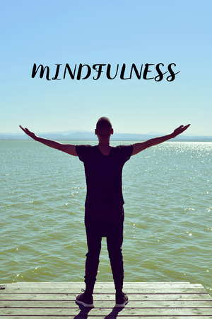 prana: a young caucasian man seen from behind with his arms in the air saluting the new day in front of the sea and the text mindfulness Stock Photo