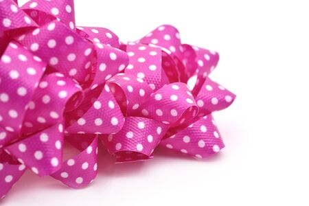 loopy: closeup of some gift puff bows made with pink ribbon patterned with white dots, on a white background Stock Photo
