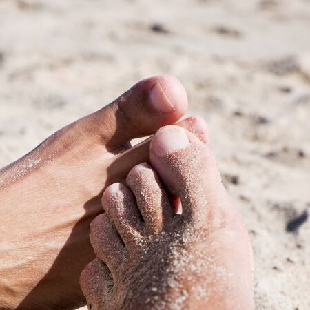 footsie: closeup of the feet of two young men playing footsie on the beach