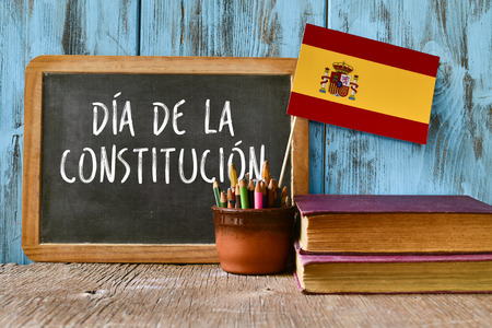 spaniards: a chalkboard with the text dia de la constitucion, constitution day written in spanish, a pot with pencils, the flag of Spain and some old books, on a rustic wooden surface