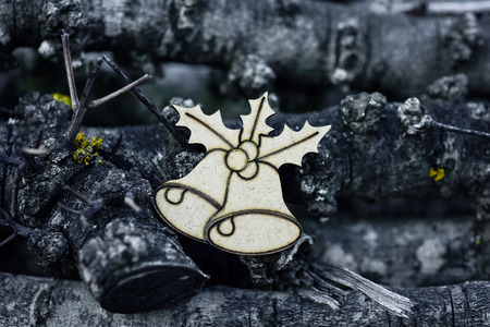 yule log: wooden ornament in the shape of two bells and a twig of holly, on a pile of logs