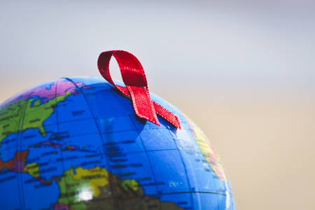 closeup a world globe with a red ribbon for the fight against AIDS Stock Photo