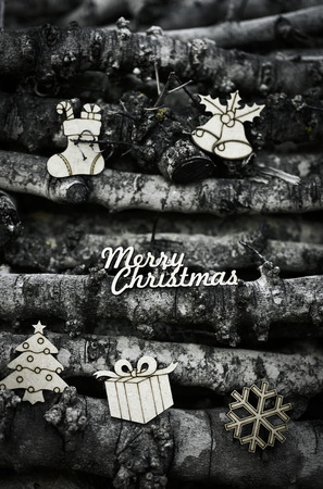 homelike: the text merry christmas and some wooden christmas ornaments, such as a christmas tree, a christmas stocking or a gift, on a pile of logs