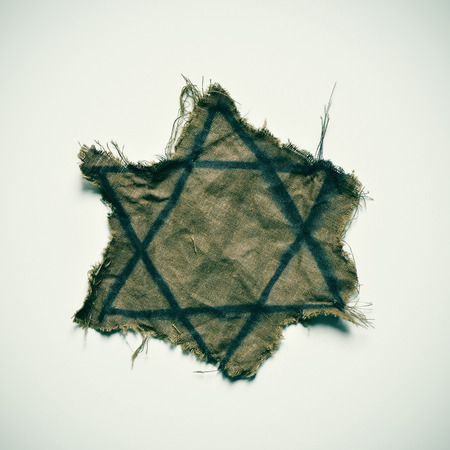 nazism: closeup of a ragged Jewish badge on an off-white background