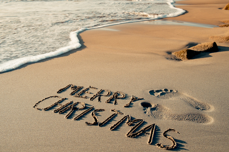 some foot prints and the text merry christmas written in the sand of a beach stock - Merry Christmas Beach Images