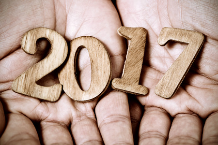 0 1 year: closeup of wooden numbers forming the number 2017, as the new year, in the hands of a young caucasian man Stock Photo