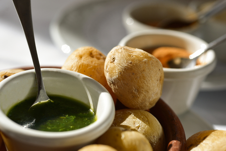 closeup of a plate with some papas arrugadas, typical Canarian wrinkly potatoes, and bowls with different mojo sauces, green mojo and red mojo or mojo picon
