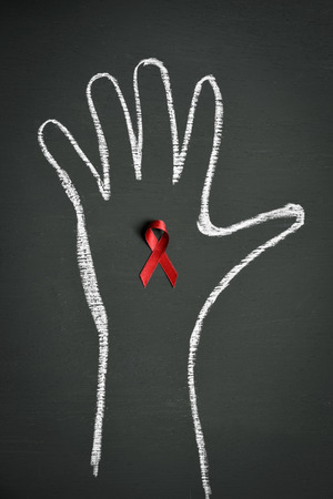 acquired: a red ribbon for the fight against AIDS pinned in a chalkboard with a hand drawn with chalk in it Stock Photo