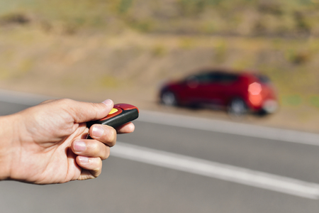 keyless: closeup of a young caucasian man opening or closing his car with the control remote key parked next to the road Stock Photo