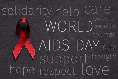 deficiency: a red ribbon for the fight against AIDS, the text world aids day and some other words relative to it, like hope, help, care, support or awareness, on a dark gray surface