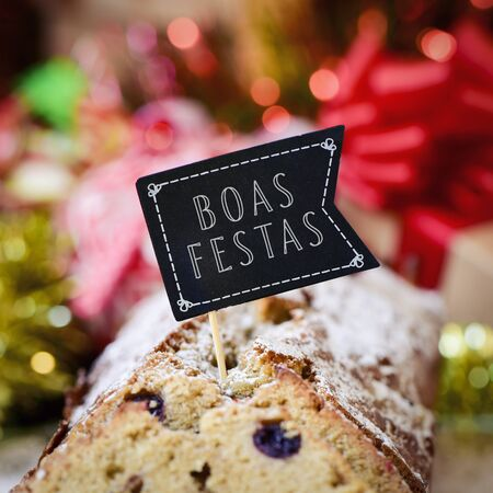 boas: closeup of a fruitcake topped with a flag-shaped signboard with the text boas festas, happy holidays written in portuguese, on a table full of christmas gifts and ornaments