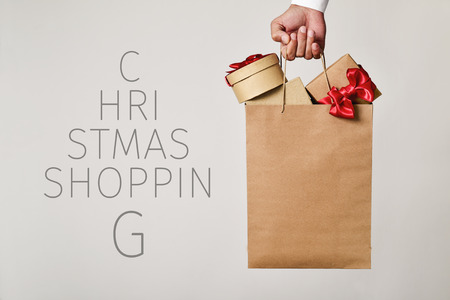 closeup of the hand of a young caucasian man holding a paper shopping bag full of gifts and the text christmas shopping forming a christmas tree Archivio Fotografico