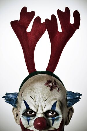 closeup of a scary evil clown wearing a reindeer antlers headband staring at the observer Stock Photo