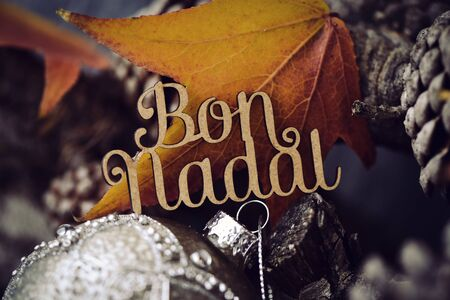 nadal: the text bon nadal, merry christmas in catalan, made in wooden and some dry leaves, some pine cones and an ornamented christmas ball