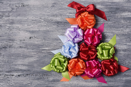 loopy: some satin gift ribbon bows of different colors forming a christmas tree on a rustic wooden background, with a negative space