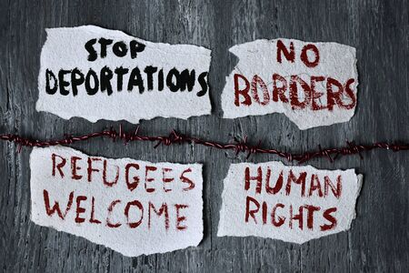 displaced: high-angle shot of a barbed wire and some pieces of paper with different messages, such as stop deportations, no borders, refugees welcome and human rights written in them, on a rustic wooden surface