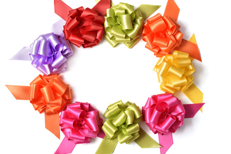 loopy: some satin gift ribbon bows of different colors on a white background forming a circle, with a negative space in the center