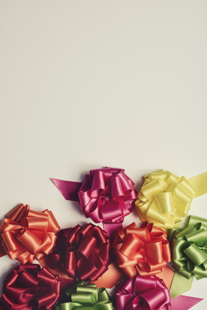 loopy: some satin gift ribbon bows of different colors on an off-white background, with a negative space and a retro effect