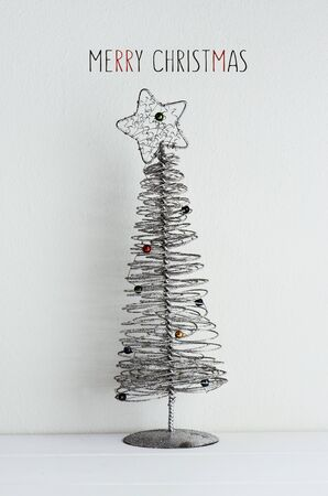 A Simplified Christmas Tree Made Of Wire Placed On An Off-white ...