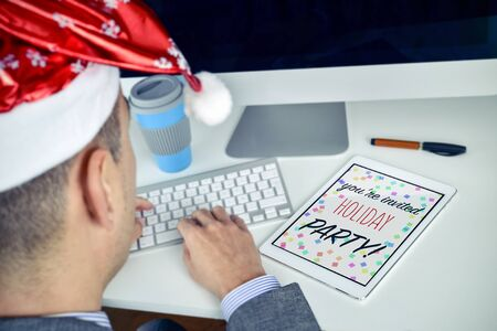 headman: a young caucasian man with a santa hat sitting at his office desk looking to his tablet, where you can read the text christmas party you are invited Stock Photo