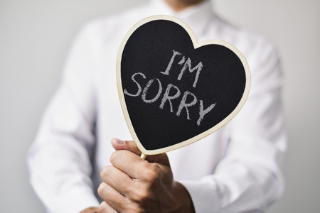 apologise: a young caucasian man wearing a white shirt shows a heart-shaped signboard with the text I am sorry written in it
