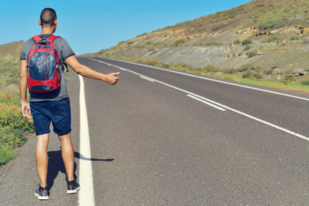 itinerant: a young caucasian man seen from behind carrying a backpack hitchhiking in a minor road, with his thumb up