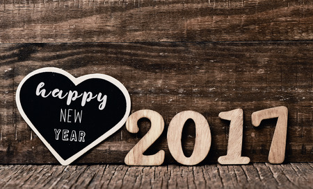 0 1 year: heart-shaped black signboard with the text happy new year written in it and some wooden numbers forming the number 2017 placed on a rustic wooden surface Stock Photo