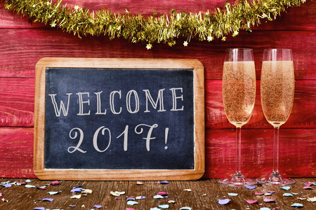 welcome party: a chalkboard with the text welcome 2017 written in it, some confetti and a pair of glasses with champagne on a red rustic wooden background ornamented with tinsel