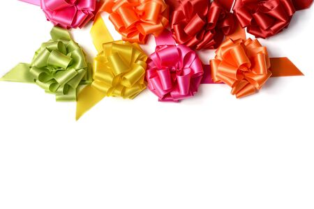 loopy: some satin gift ribbon bows of different colors on a white background, with a negative space