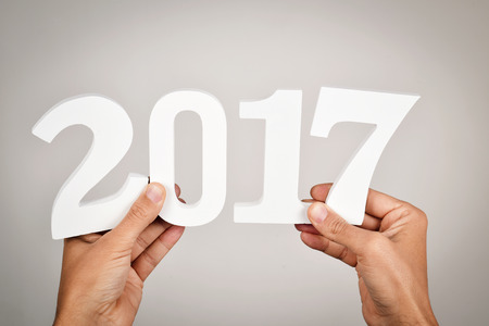 young man holding some white numbers forming the number 2017, as the new year Stock Photo